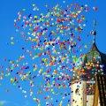 Farverige balloner stiger op ved kirketårn