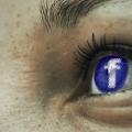 Nærbillede af ansigt med facebook logo i øjnene.