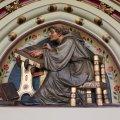Relief af munk der sidder og afskriver en Bibel