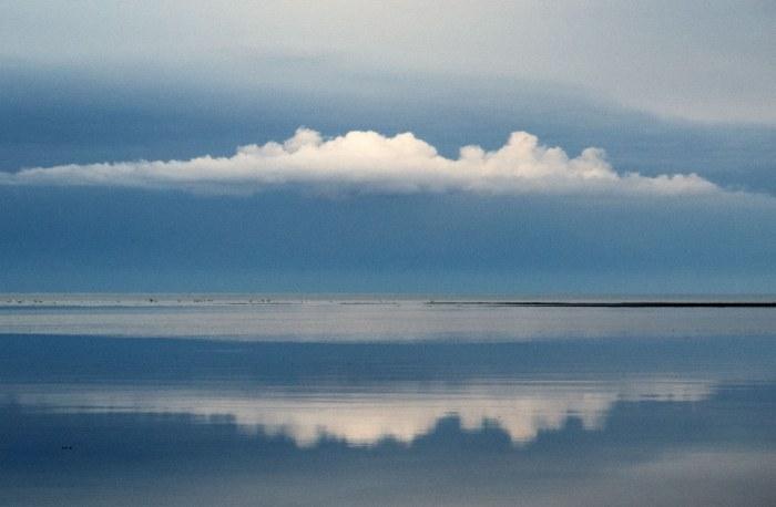 Skyer spejler sig i havet