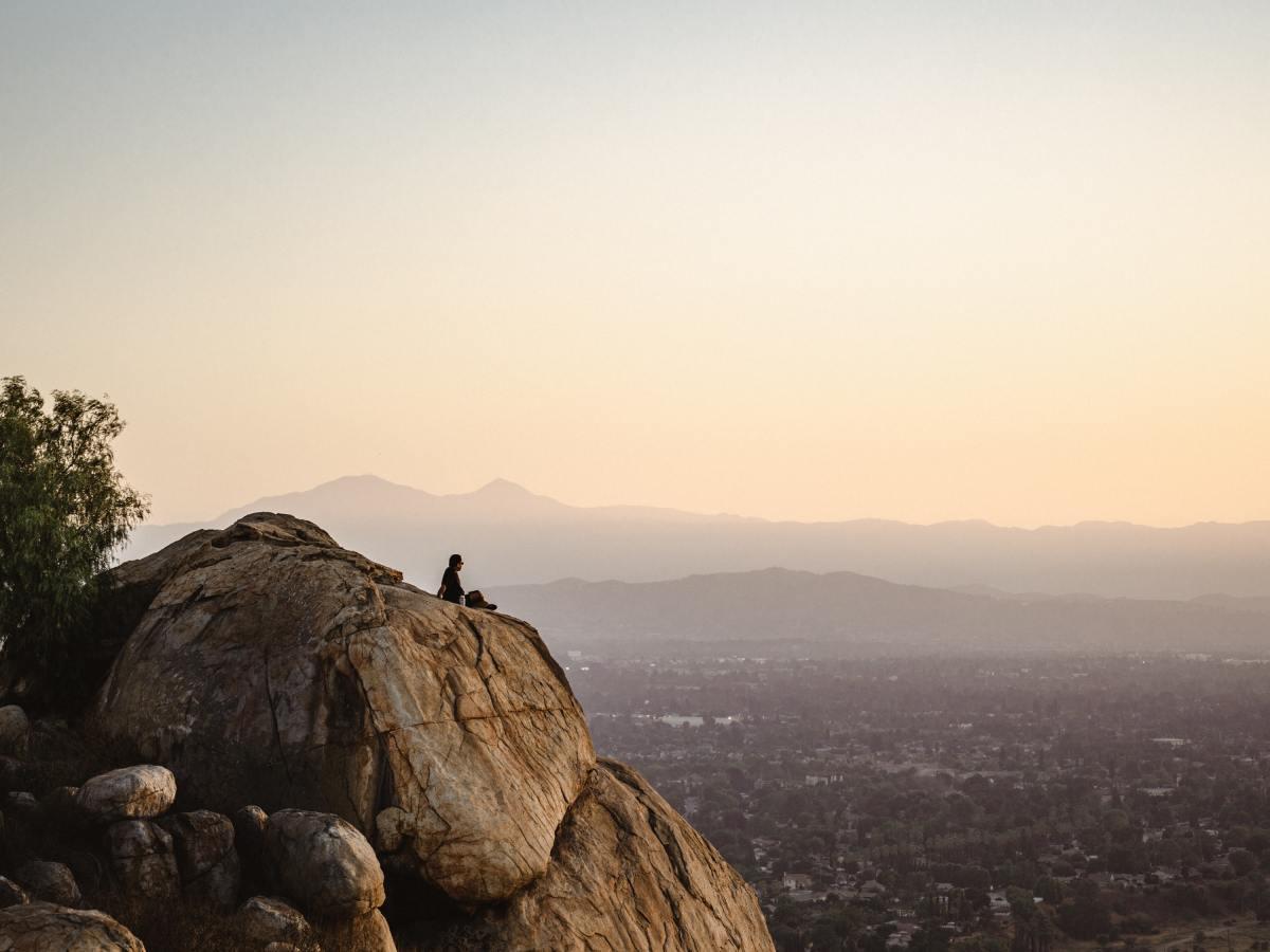 Mand sidder på Bjerg og kigger ud over by